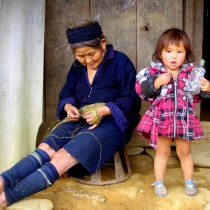 Grandma weaving hemp and granddaughter